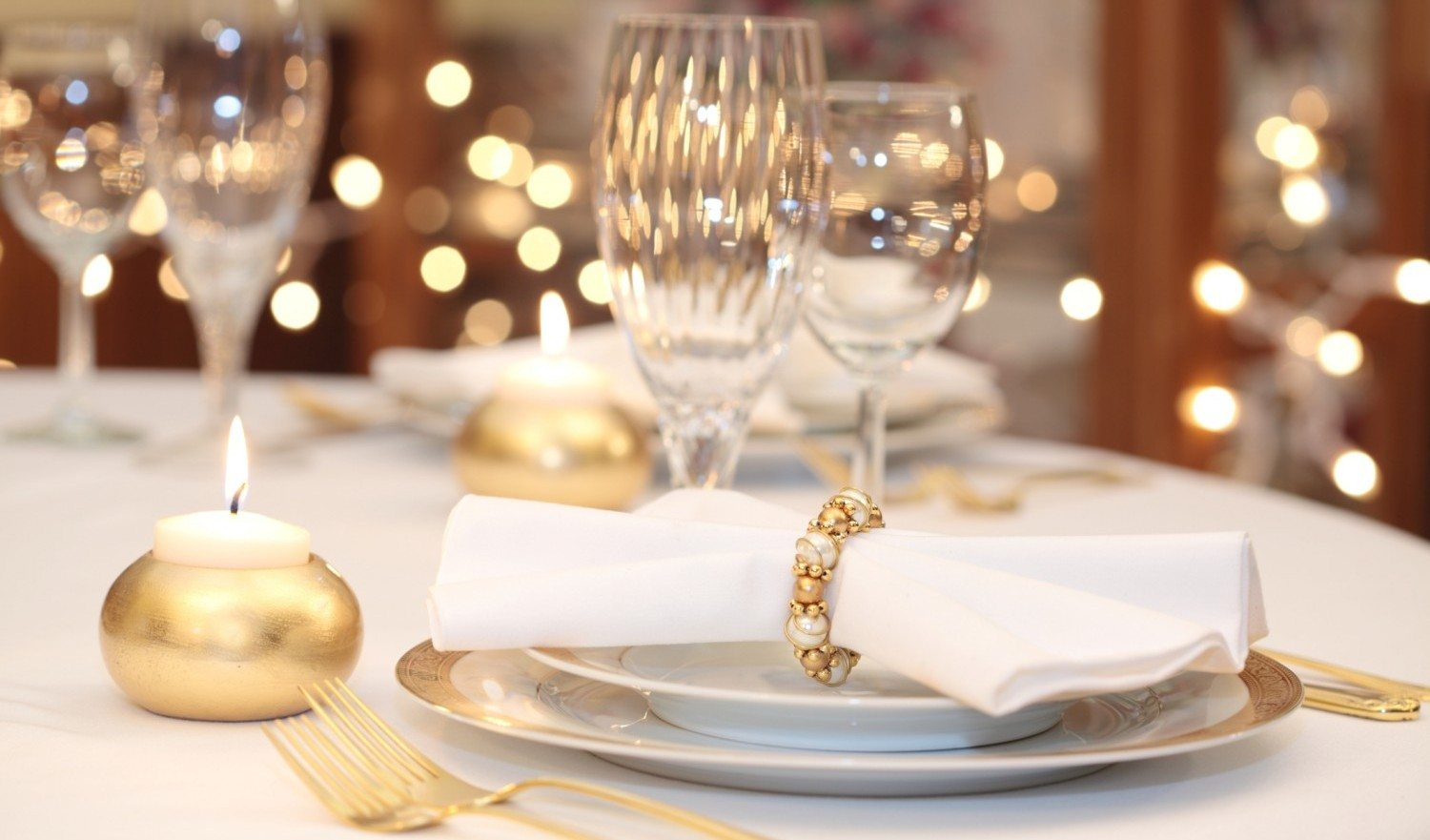 Elegant place setting in gold, white and clear crystal. Gold candle holder with burning candle. Lights in background are out of focus. Shallow depth of field.