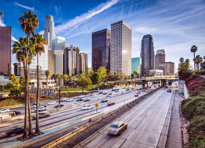 Cityscape view of downtown Los Angeles, California. Freeway drivers speed past palm trees and tall buildings on a sunny day.