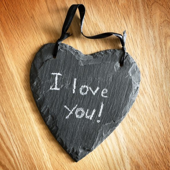 """I love you"" written on a black stone in the shape of heart, similar to the blackboard surface."