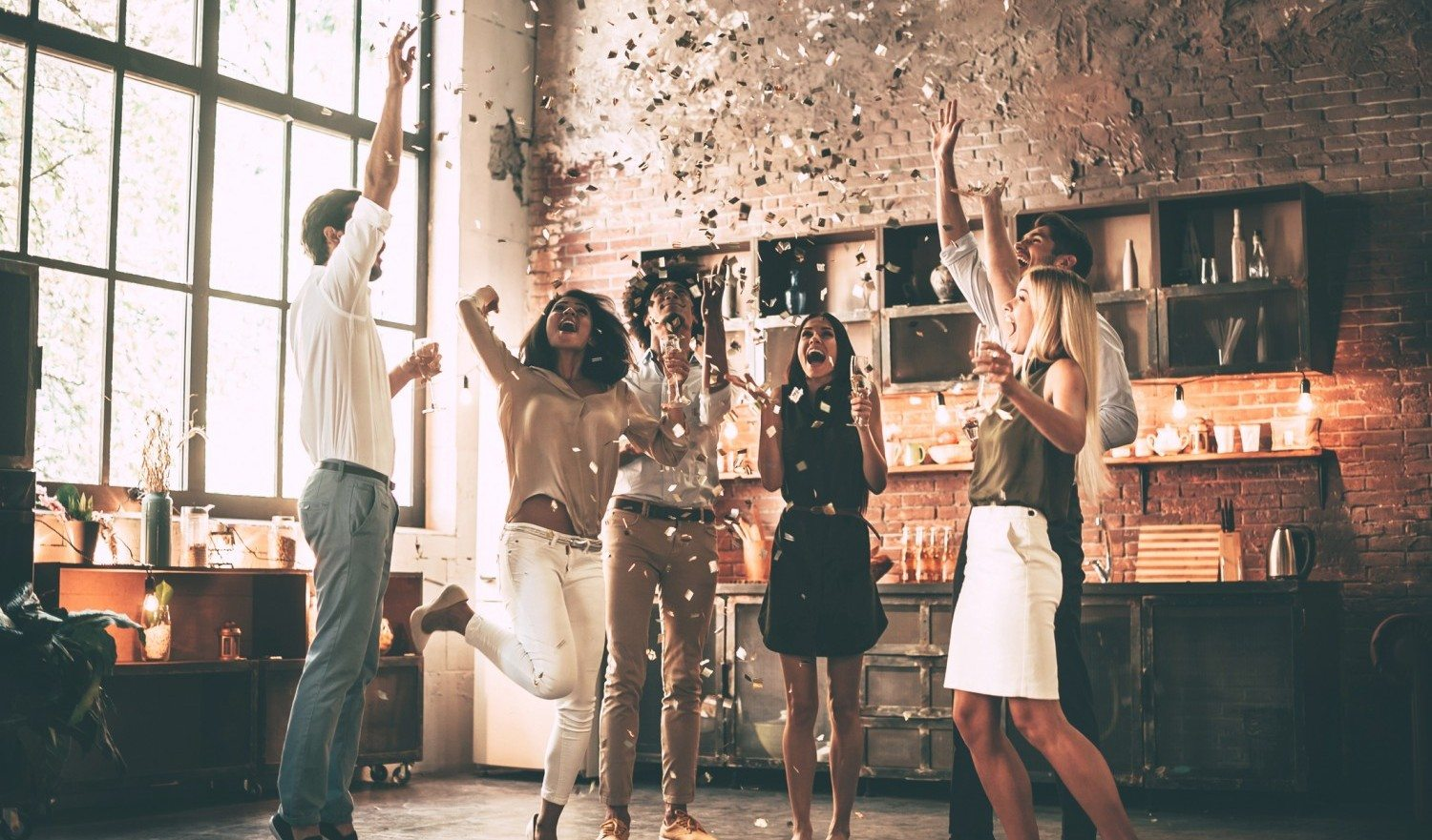 Full length of cheerful young people throwing confetti and jumping while enjoying home party on the kitchen