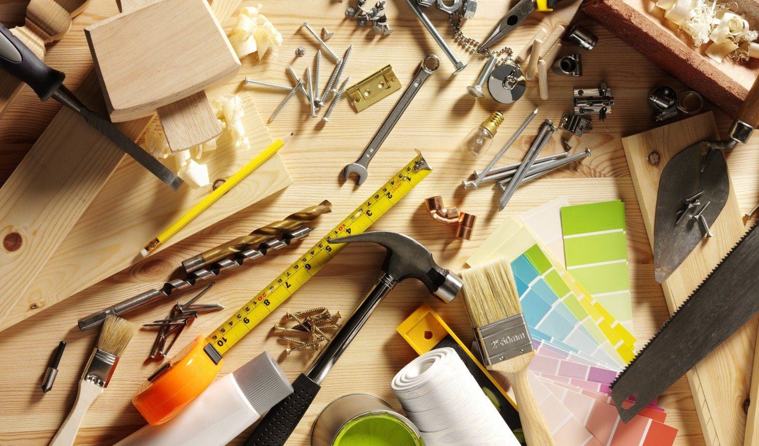 """Work tools and products such as a spanner and screws, hinges, sink plug, screws, raw plugs, jubilee clips, brass pipe and socket set pieces. Home decorating with paint, building bricks, wood, samples, hammer and many more tools for DIY on a wooden background. Overhead view.Click on the link below to see more DIY and Tool images."""