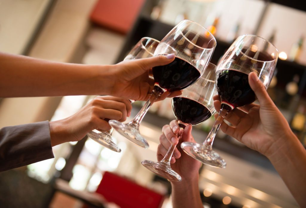 Group of unrecognizable friends making a toast with red wine