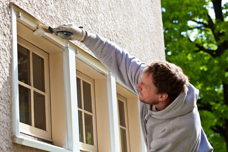 A professional house painter, small construction business entrepreneur, home owner or handyman works on exterior wooden surface, painting house window trim for repair and home improvement. The working man wears a painting cap, protective work gloves, and hooded sweatshirt, carefully brushing the paintbrush to apply latex paint for fall maintenance.