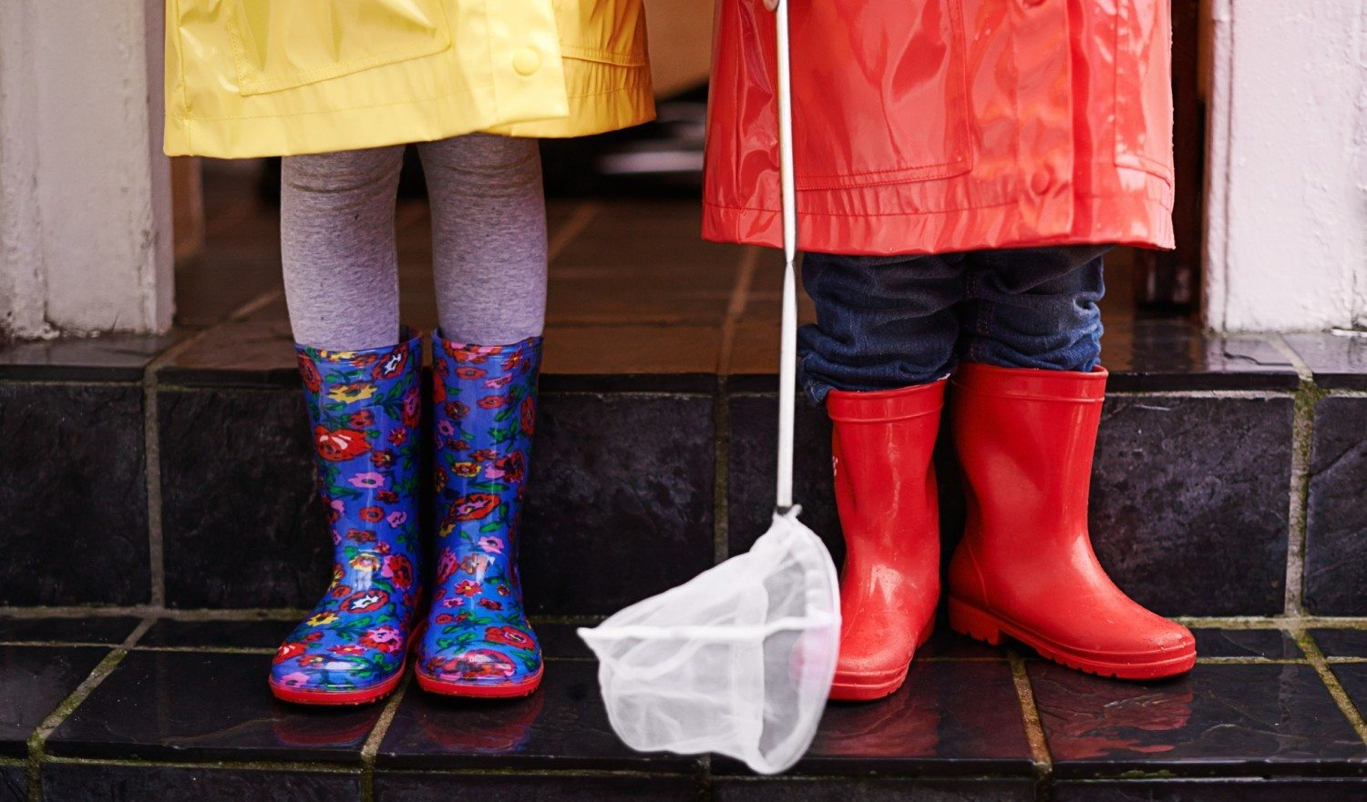 Cropped shot of two children dressed in raincoats and galoshes