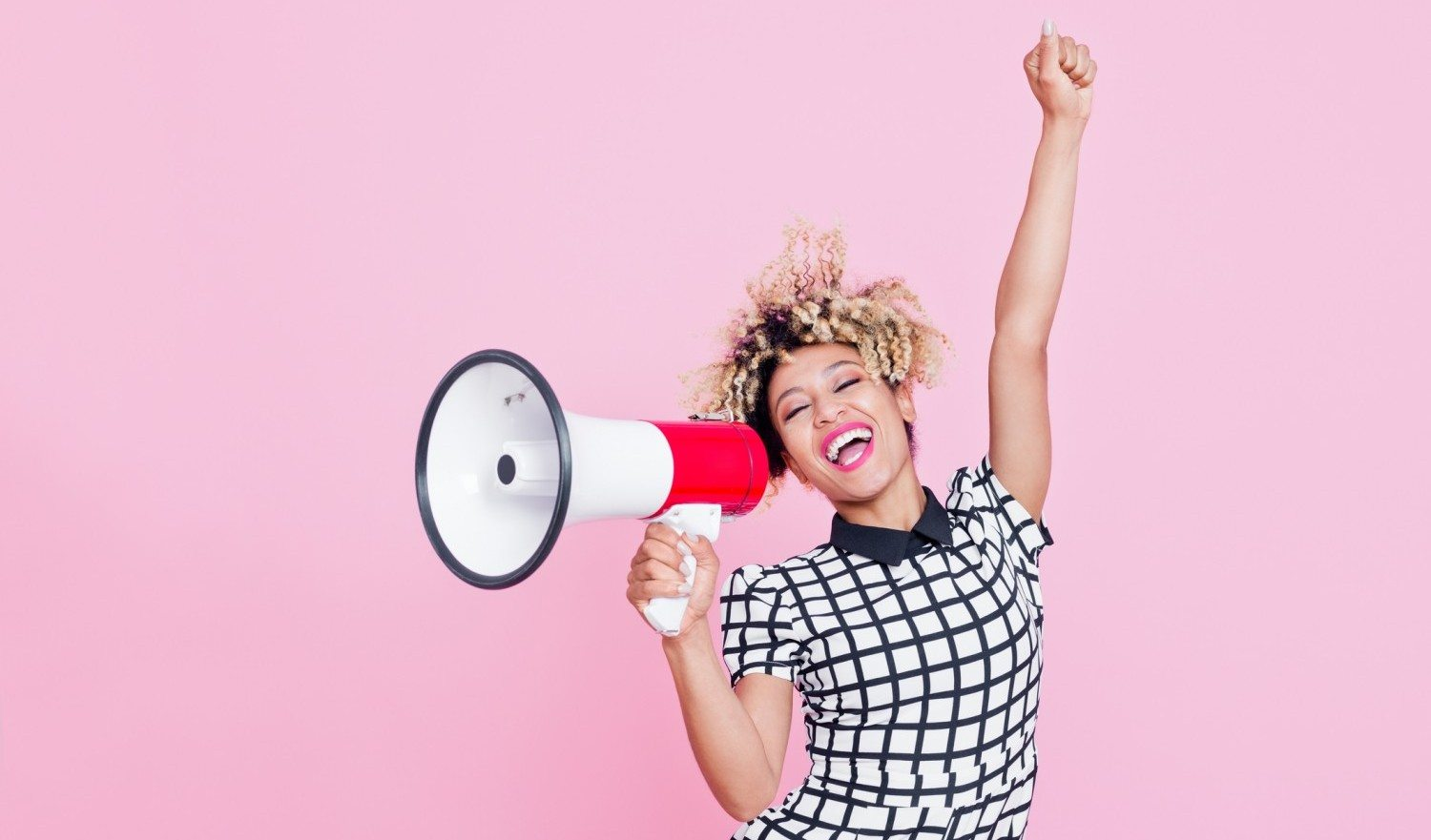 Summer portrait of beautiful afro american young woman, wearing grid check playsuit, standing against pink background, shouting into megaphone. Studio shot.