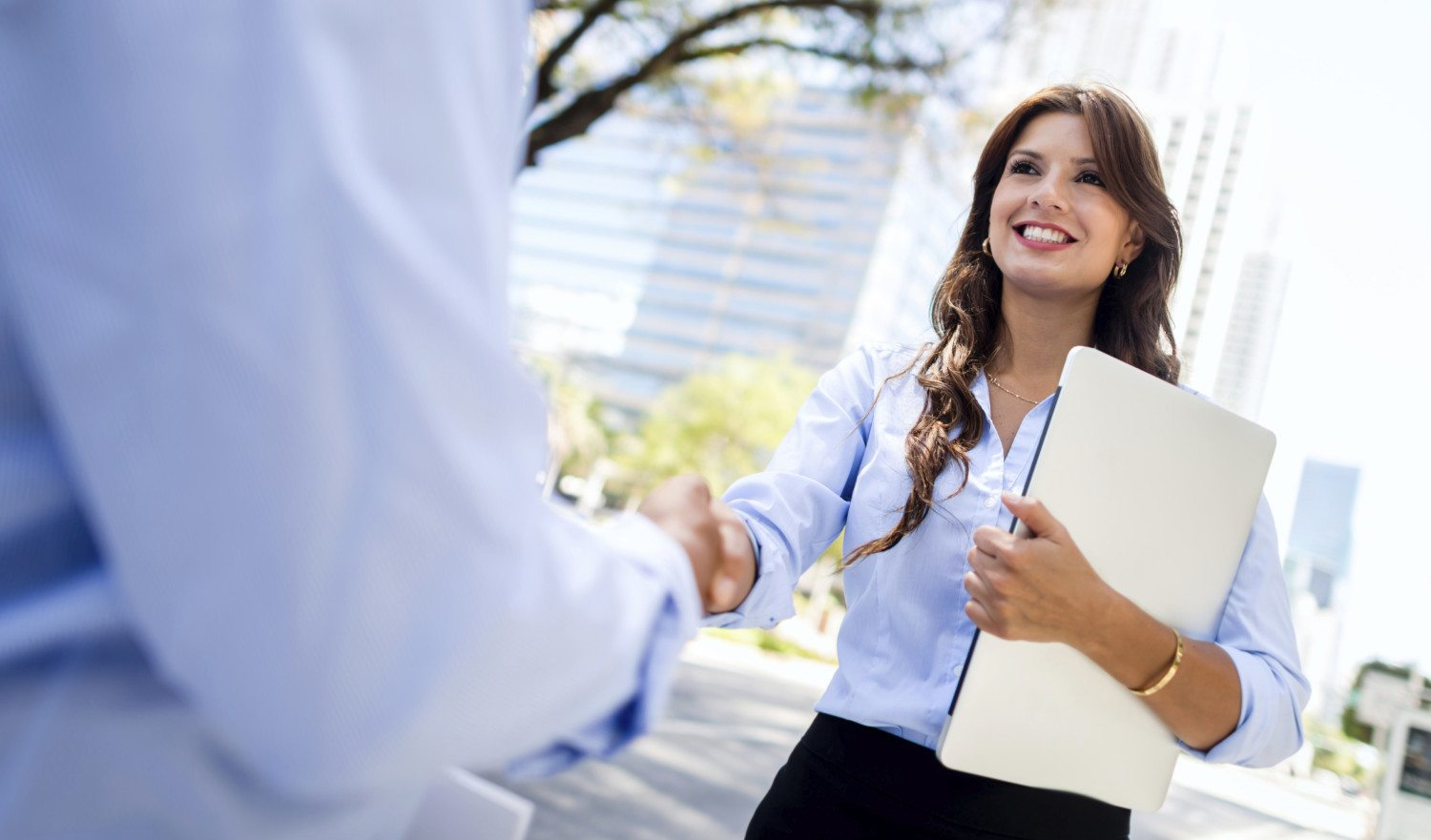 Business woman handshaking with a client - outdoors