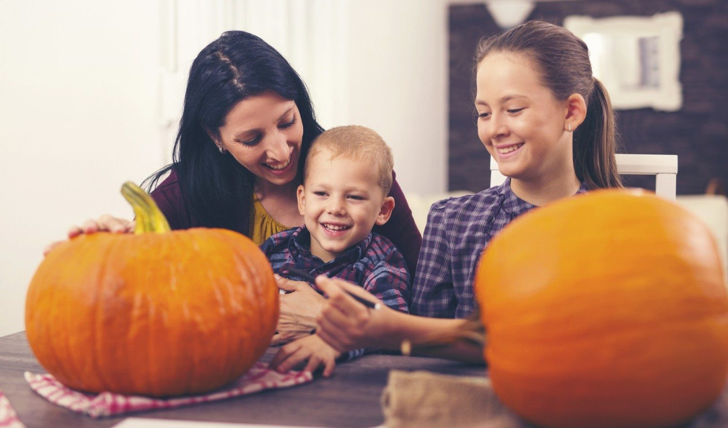 Mother with daughter and son creating big orange pumpkin