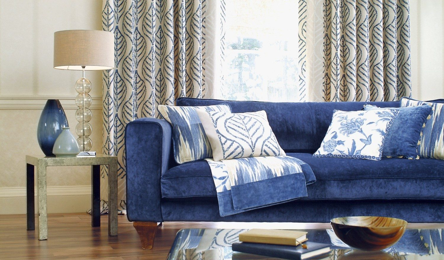 Blue sofa in a window on sunny day with table in foreground