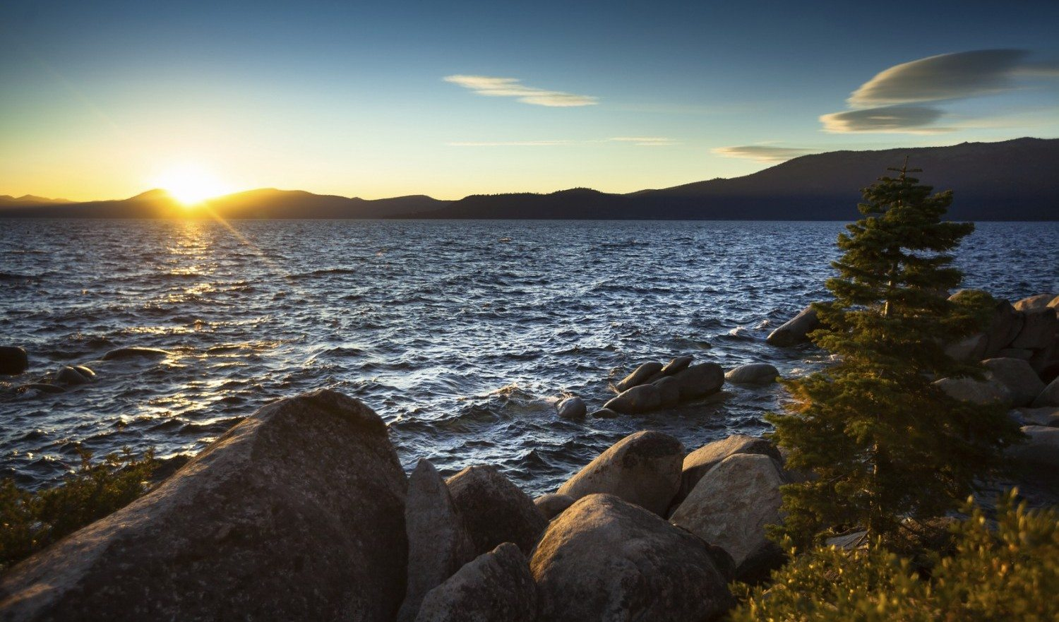 The evening sun begins to hit the horizon, making everything glow brightly in this view from a camping spot at Sand Harbor State Beach at Lake Tahoe
