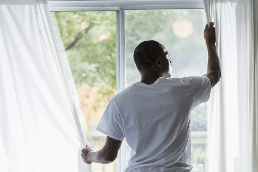 Rear view of a young black man opening the white curtains to let in the morning sunlight.  His face is visible enough to see his serious expression.