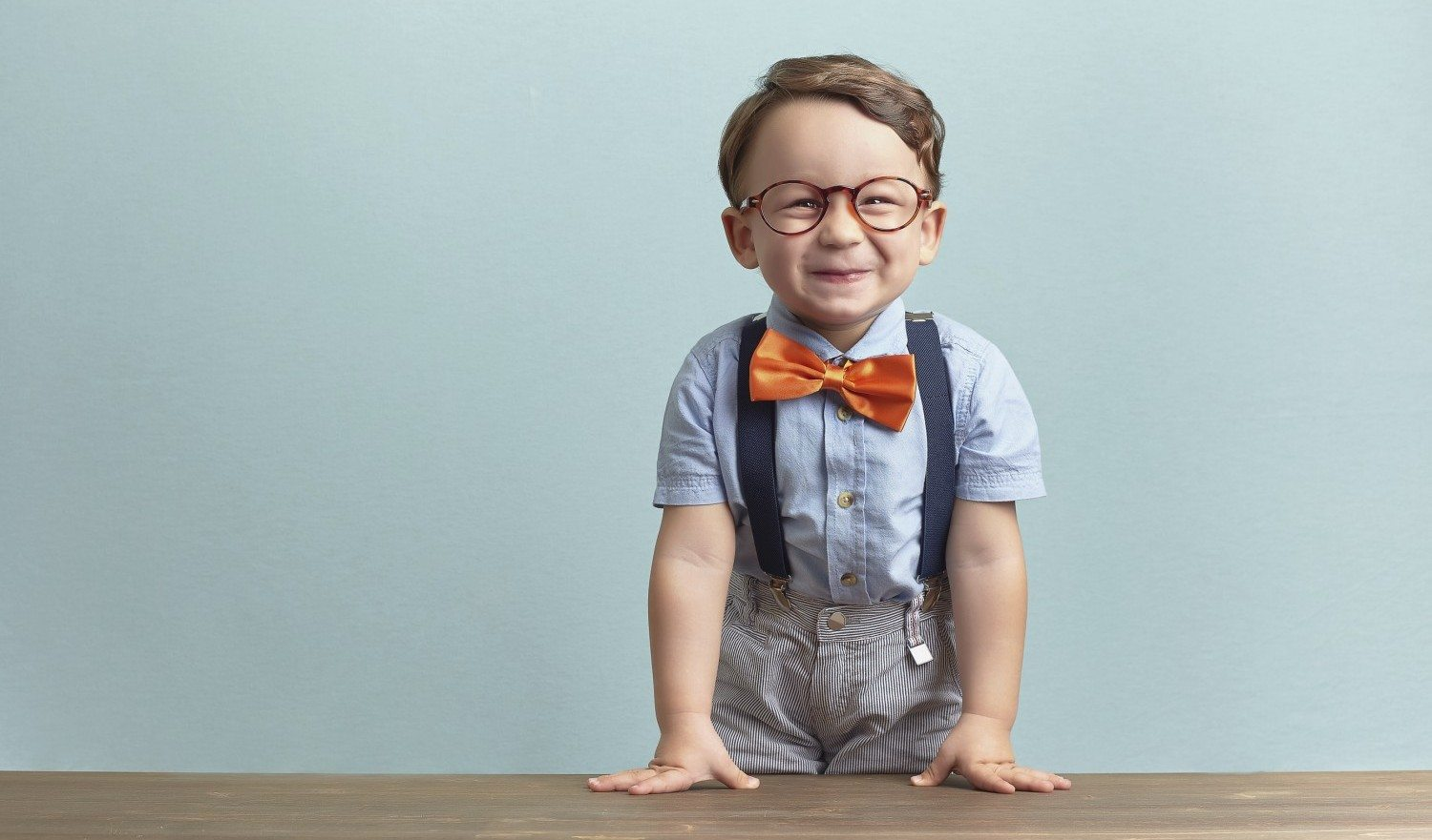 Around three years old boy in an orange bow tie and glasses, wearing blue shirt. He put his hands on the brown table, seems to be happy and joyfull over baby-blue backgorund. He squints and his teeth are seen. Photo was taken by Canon DSLR