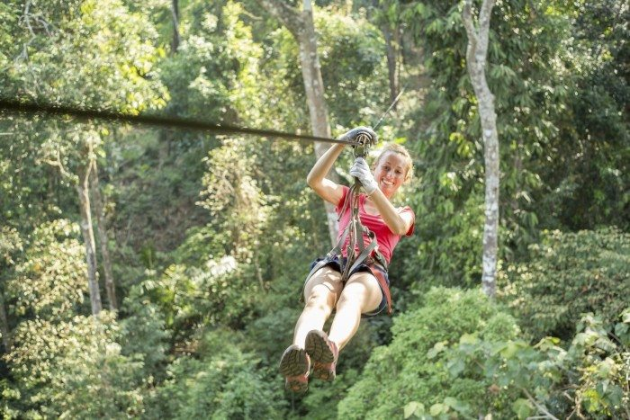 Young healthy woman enjoying zip-lining on a canopy tour adventure in the rain forest in northern Laos, sunny summer day.