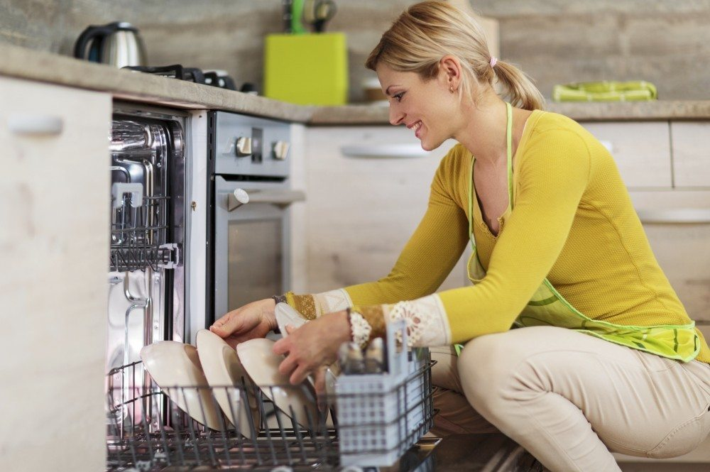 Happy young woman crouching and using dishwasher in the kitchen.