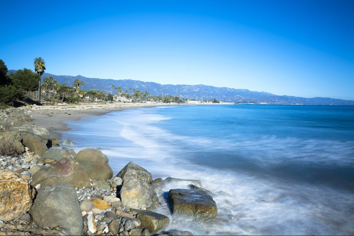 Image of a long exposure during a period where waves are approaching a sandy and rocky beach in Santa Barbara California