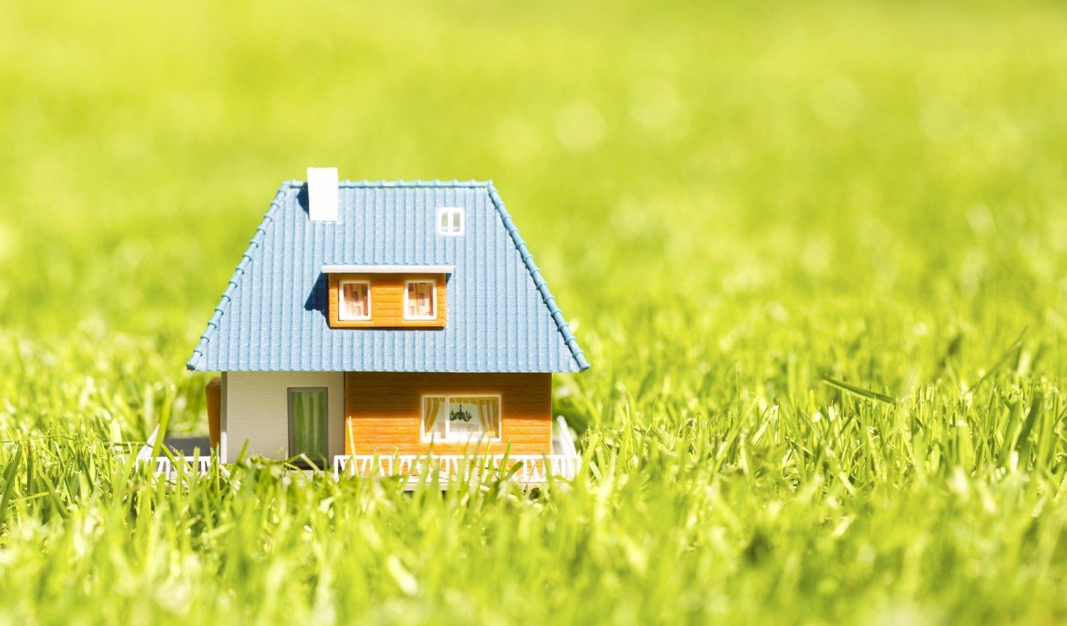 plastic house scale model on green grass with copy space