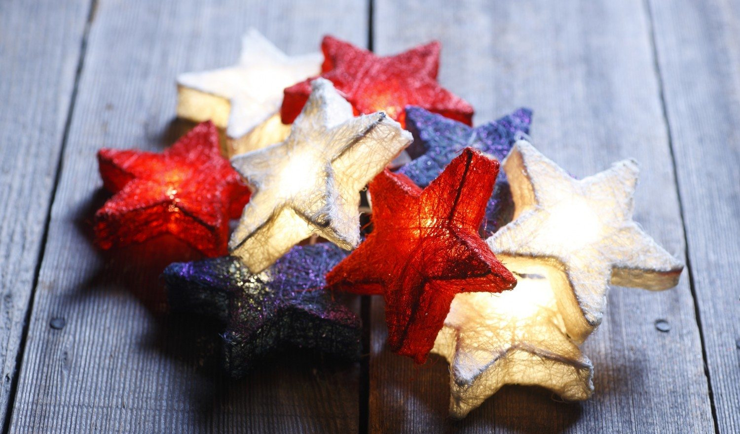 Pile of Red, White, and Blue stars on distressed wood surface