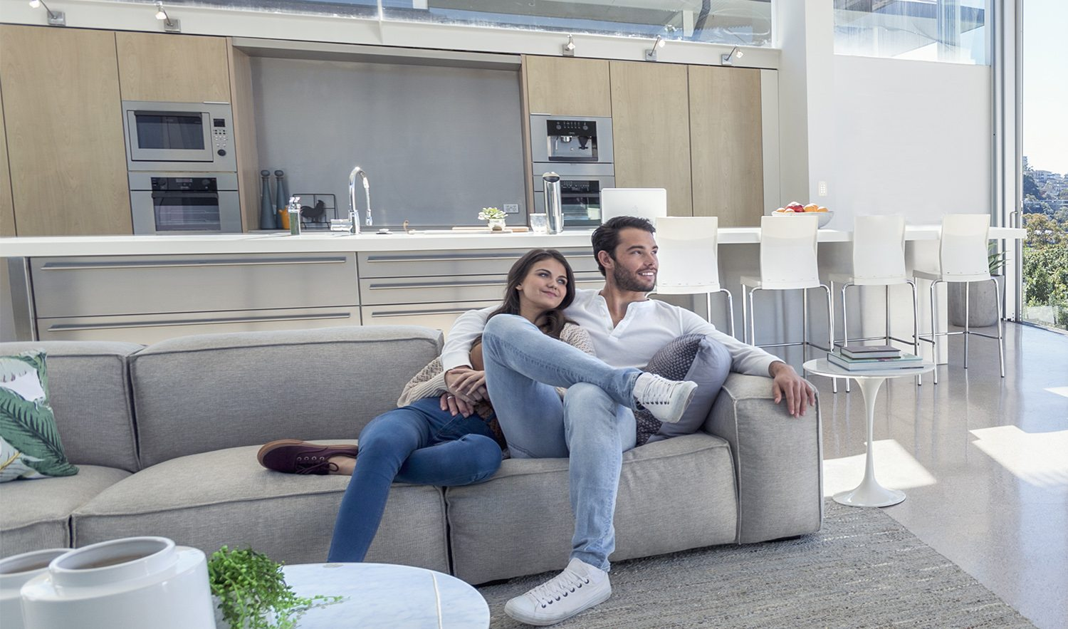 Couple sitting in a modern open plan house. They are sitting on a sofa with a kitchen behind them. They are looking at the beautiful water view from their house. They are attractive, smiling and happy.